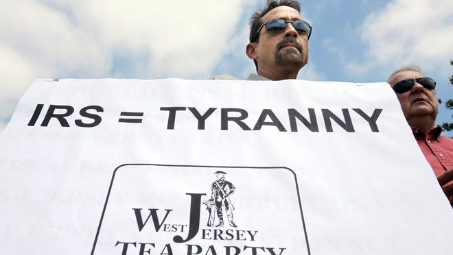 Keith Peacock holds a sign during a Tea Party rally protesting extra IRS scrutiny of their groups on May 21 in Cherry Hill, N.J.