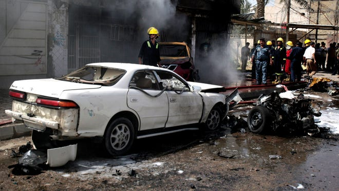 Iraqi security force members inspect the site of a car bomb attack in Basra, 340 miles southeast of Baghdad, Iraq, Sunday, June 16, 2013.