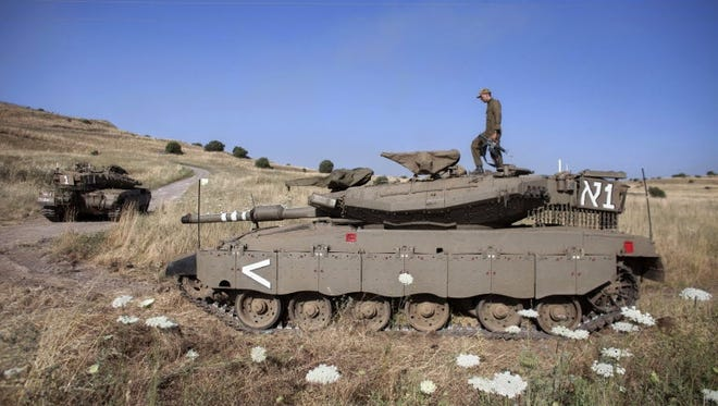 An Israeli soldier walks atop a tank near the Quneitra crossing to Syria on June 6.
