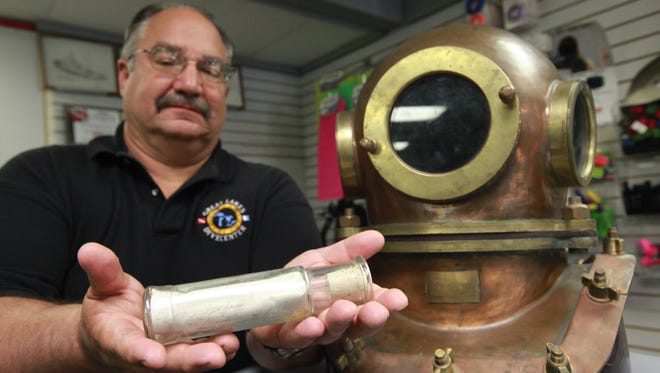 David Leander, owner of Great Lakes Divecenter in Michigan's Shelby Township, holds on Sunday, June 16, 2013, a message in a bottle he found buried along Harson's Island since 1915.