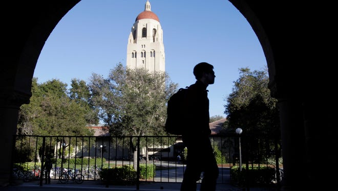 A Stanford University student walks in front of Hoover Tower on the Stanford University campus in Palo Alto, Calif., in 2012.