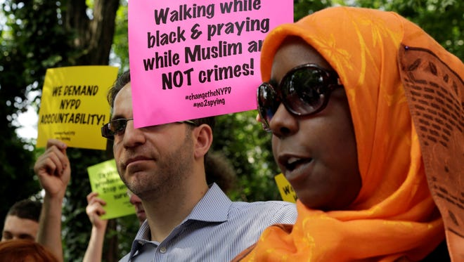 Supporters of a lawsuit challenging the NYPD's Muslim surveillance program, hold signs during a gathering on a plaza in front of New York City Police Department headquarters, June 18.