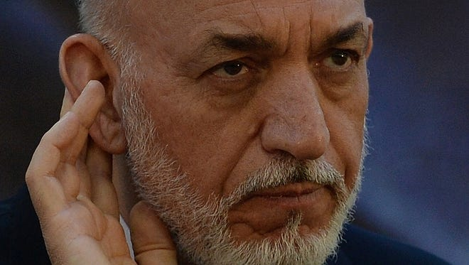 Afghan President Hamid Karzai listens to a journalist's question during a joint press conference with NATO Secretary General Anders Fogh Rasmussen after a security handover ceremony at a military academy outside Kabul on June 18, 2013.