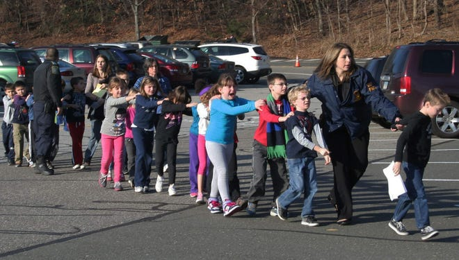 Connecticut State Police lead a line of children from the Sandy Hook Elementary School in Newtown, Conn. after a shooting at the school in December 2012. Connecticut passed stricter gun control legislation after the shooting, prompting gun manufacturers to threaten to leave the state. PTR Industries plans to announced that it will relocate to South Carolina.