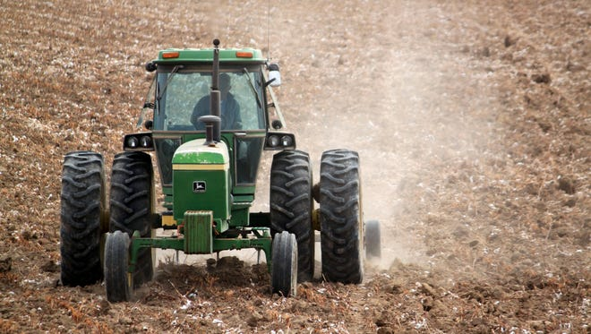 In this March 19, 2013 photo, a tractor plows a cotton field in Hatch, N.M., in preparation for the spring growing season.