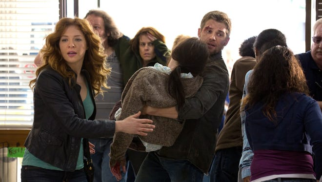 Newspaper editor Julia Shumway (Rachelle Lefevre) and military veteran Dale 'Barbee' Barbara (Mike Vogel) tend to the injured after the dome falls.