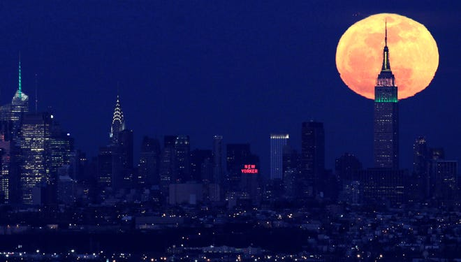 A full moon rises behind the Empire State Building in New York in April 2012. This weekend, a supermoon will rise over the USA.