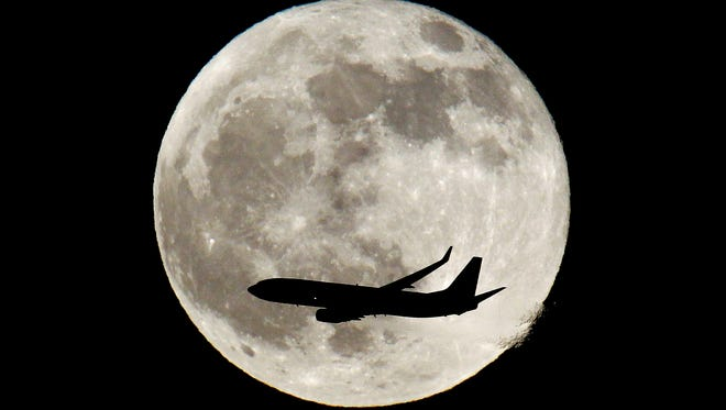 It is shorter to fly the Great Circle route than a straight line due to the circumference of the earth being so much greater at the equator than near the poles. Here, a plane flies over the northern New Jersey sky with the full moon in the background.