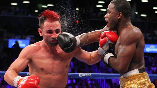 Adrien Broner, right, and Paulie Malignaggi  trade punches during their 12 round WBA welterweight championship bout Saturday. Broner won by split decision.