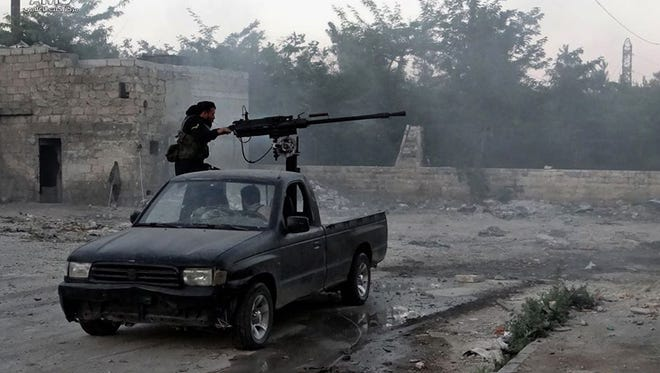 A Syrian rebel in Aleppo fires a machine gun Thursday toward soldiers loyal to the Assad regime.