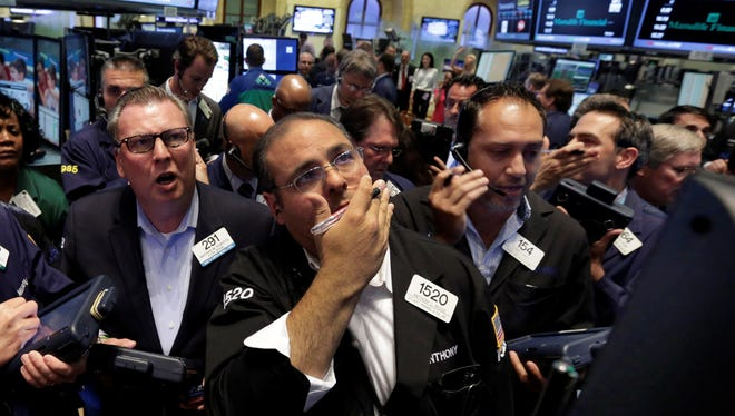 Traders gather at the post on the floor of the New York Stock Exchange.