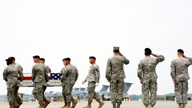 An Army carry team moves a transfer case containing the remains of Maj. Jaimie E. Leonard on Wednesday, June 12, 2013, at Dover Air Force Base, Del.