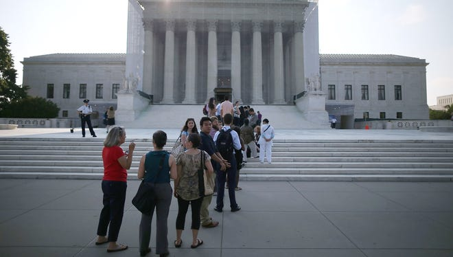 People wait to enter the Supreme Court on Monday to hear some of the court's final-week decisions.