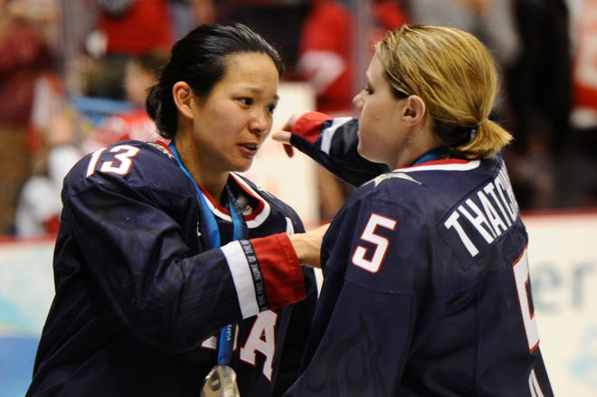 Julie Chu greets USA's Karen Thatcher after the medal ceremony for the Americans' 2-0 loss to Canada at the 2010 Olympics in Vancouver. Chu was named to the U.S. national team training for the Sochi Games.