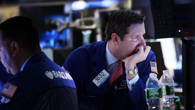 Traders work on the floor of the New York Stock Exchange (NYSE), as worries mount about the slowing economy.