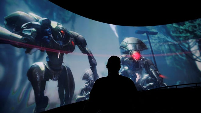 Alex Beckers watches a presentation of the video game 'Destiny' at the Activision-Blizzard booth during the Electronic Entertainment Expo in Los Angeles