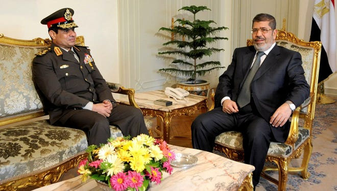 Egyptian Minister of Defense, Lt. Gen. Abdel-Fattah el-Sissi, left, meets with Egyptian President Mohammed Morsi at the presidential headquarters in Cairo, Egypt, Feb. 21, 2013.