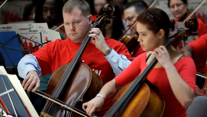 Cellist and music teacher Eric Jones, left, play in a farewell concert with music teachers slated to lose their jobs and former students at the Philadelphia school district's headquarters, June 24, in Philadelphia.
