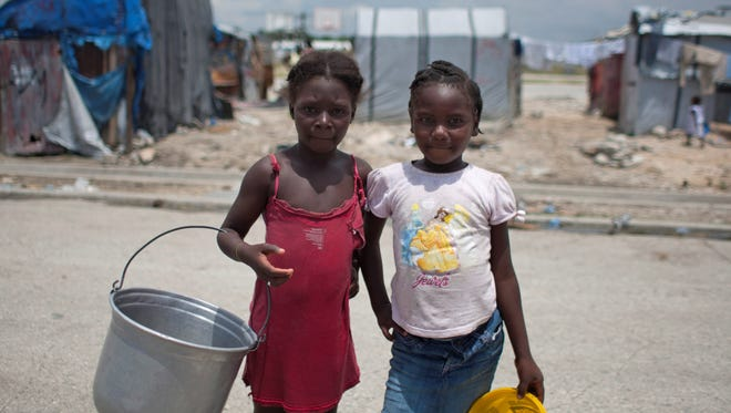 Alix Milanda, 9, left, poses for a picture with her friend Shella St-Telise, 9, as they look for water at the Jean-Marie Vincent camp for people displaced by the 2010 earthquake, in Port-au-Prince, Haiti, April 22.