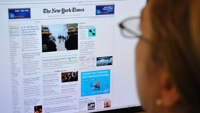 A woman reads the front page of the New York Times on the Internet in October 2010.   The New York Times and other large newspapers have begun requiring online subscriptions.