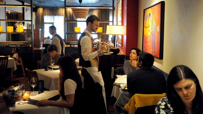 Server Thom Mathis tends to guests as they dine at Rick Bayless' Topolobampo restaurant in Chicago.