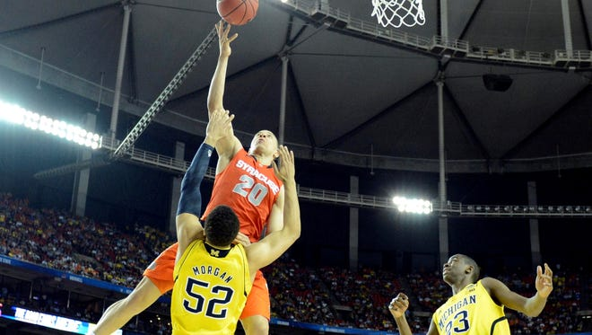 Syracuse guard Brandon Triche (20) is called for an offensive foul against Michigan forward Jordan Morgan (52)  in the second half of the semifinals during the 2013 NCAA men's Final Four at the Georgia Dome.