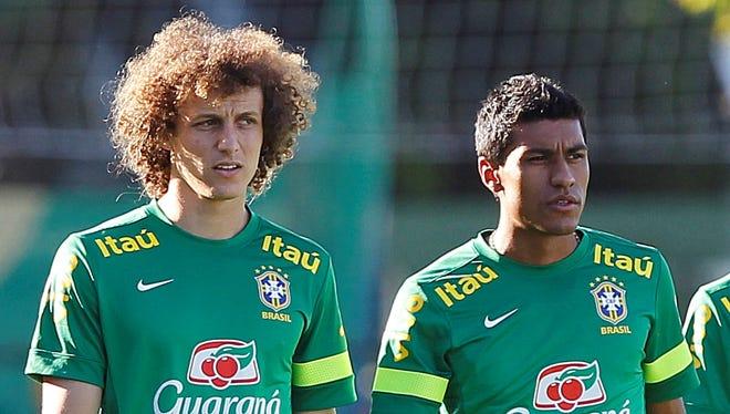 David Luiz, left, and Paulinho attend a training session in Goiania, Brazil.