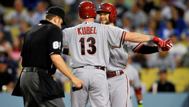 Arizona Diamondbacks left fielder Jason Kubel is greeted at home plate by right fielder Cody Ross after hitting a two-run home run at Dodger Stadium.