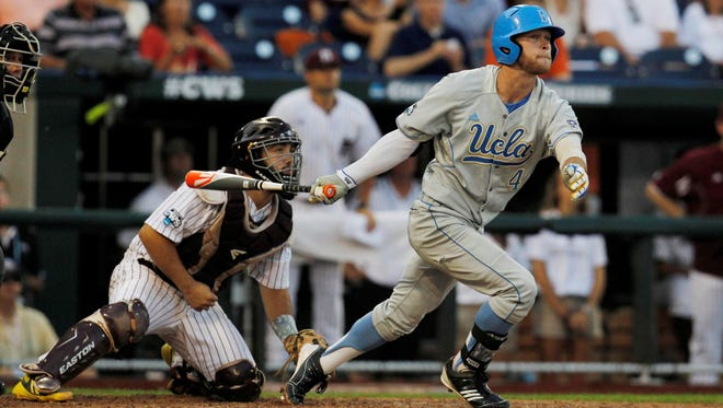 UCLA right fielder Eric Filia (4) hits a two-RBI single in front of Mississippi State catcher Nick Ammirati (left) during the fourth inning in game 1 of the College World Series finals Monday at TD Ameritrade Park.