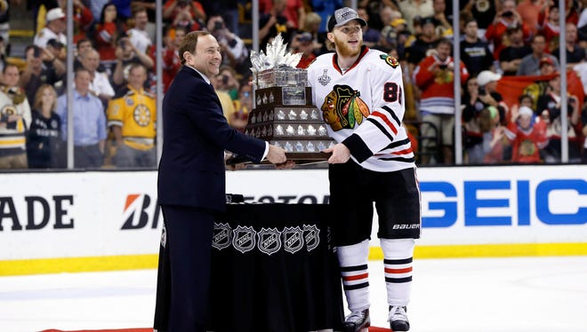 NHL Commissioner Gary Bettman (left) presents Chicago Blackhawks right wing Patrick Kane with the Conn Smythe Trophy.