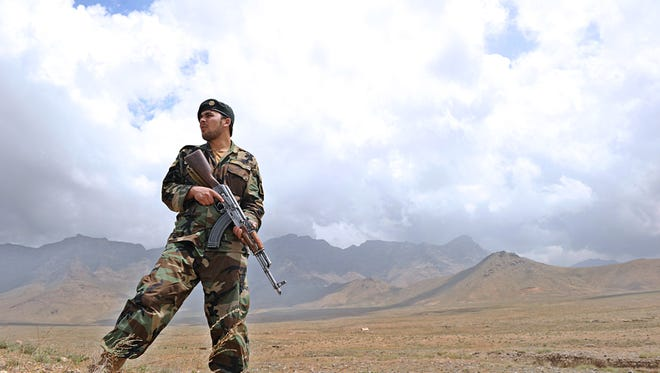 An Afghan soldier stands guard as colleagues prepare to destroy ammonium nitrate, a fertilizer used to make IEDs.