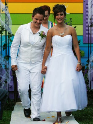 Kimberly Kidwell, left, and her partner Katie Short walk down the aisle after their wedding at the Equality House, June 22, 2013, in Topeka, Kan.