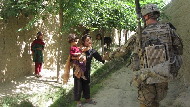 Soldier with the 1st Brigade Combat Team, 101st Airborne Division greets a young Afghan girl while patrolling a village in Khogyani District, Nangarhar Province. Later this same day, soldiers from FOB Connolly sustained an attack led by members of the Afghan Local Police, who claimed it was an accident.