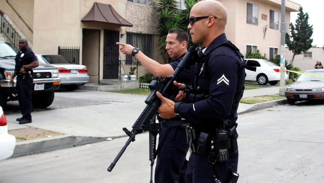 Los Angeles police officers close off and search a city street after two police officers were shot and wounded in an attack outside a police station in the Mid-City area of Los Angeles on June 25, 2013.