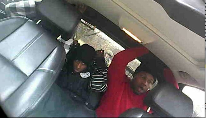 William Alexander, left, and Devin Saunders put their hands up as a team of heavily armed ATF agents surrounds them at the conclusion of a sting operation.