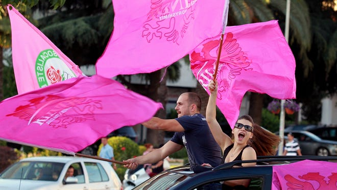 Supporters of the opposition Socialists celebrate in the Albanian capital Tirana after counting results show a clear lead of their party, June 25.