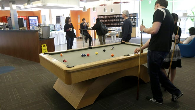 Google employees shoot pool at in a break room at the Google campus in Mountain View, Calif. A recent Gallup report said creating an good work atmosphere is more important than offering tangible perks.