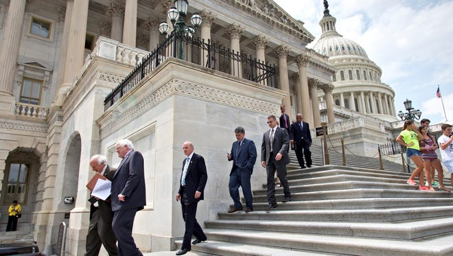 Members of the House of Representatives walk down the steps of the Capitol after final votes in Washington on June 19.