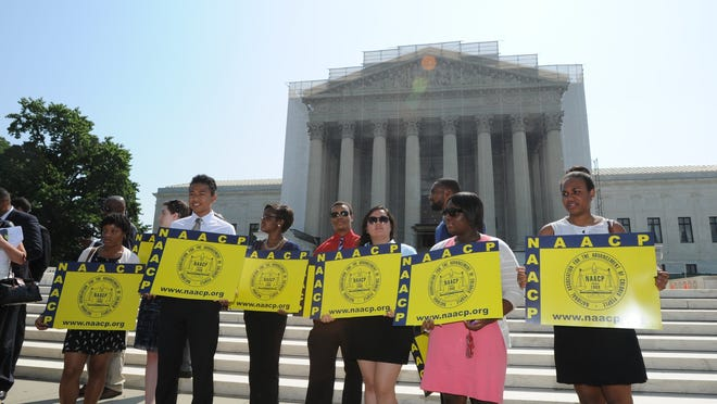Demonstrators from the NAACP stand outside the Supreme Court after the ruling striking down a key provision of the Voting Rights Act.