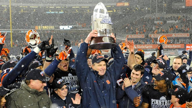 Syracuse Orange head coach Doug Marrone lifts the 2012 New Era Pinstripe Bowl Championship trophy following his teams 38-14 victory over the West Virginia Mountaineers at Yankee Stadium.