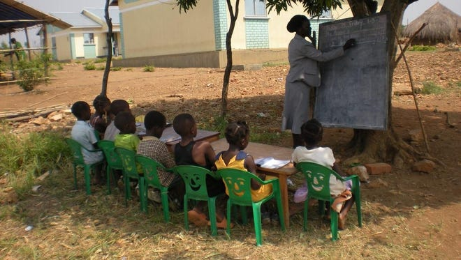 Ugandan children at Acres of Hope, a project supported by LifePoint Church in Smyrna, Tenn., study with a teacher outdoors while waiting for a school building to be completed.