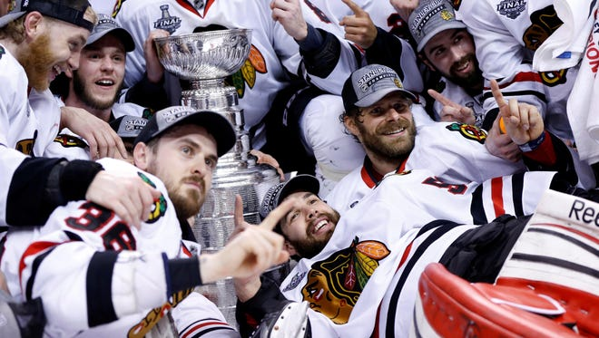 Chicago Blackhawks players pose for a team photo with the Stanley Cup after beating the Boston Bruins in Game 6.