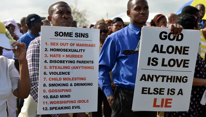Jamaican churchgoers hold signs while attending an anti-gay rally in Kingston, Jamaica, June 23.