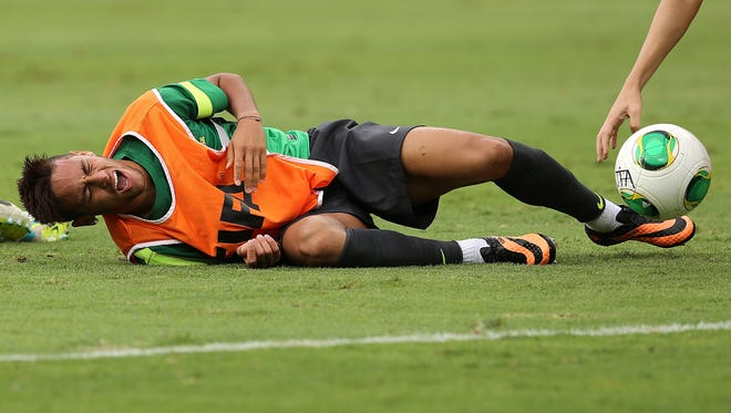 Brazil's Neymar grimaces after falling during a practice with his national soccer team at the Mineirao stadium in Belo Horizonte, Brazil on Tuesday. Brazil will play one of the semifinals of the Confederations Cup against Uruguay on Wednesday.