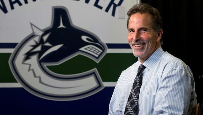 Vancouver Canucks coach John Tortorella laughs during an interview following a news conference after he was hired in Vancouver, British Columbia.