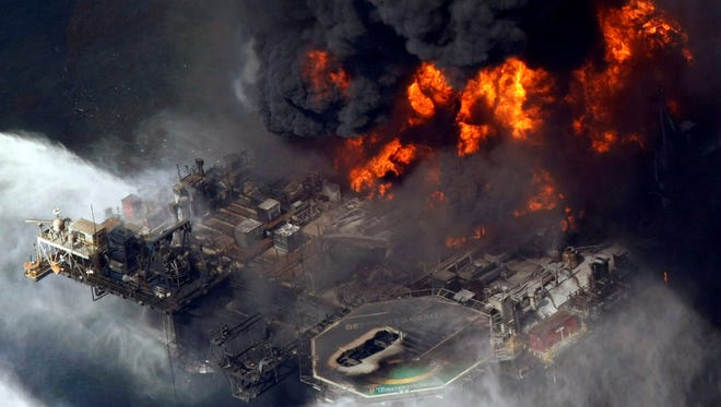 In this April 21, 2010, file aerial photo, the Deepwater Horizon oil rig burns in the Gulf of Mexico.