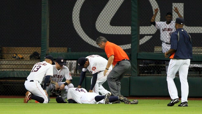 Houston Astros right fielder Justin Maxwell (44) is evaluated by medical staff after a play during the fourth inning against the St. Louis Cardinals at Minute Maid Park.