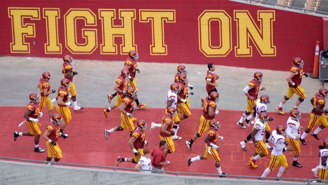 USC football players run out of the tunnel and onto the field of the Los Angeles Memorial Coliseum for their spring game on April 13. The school reached an agreement Tuesday to move ahead with a renovation of the facility, which was built in 1923.
