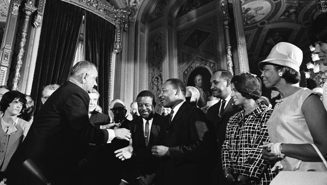 President Lyndon Johnson greets Martin Luther King Jr., far right, and activist Ralph Abernathy after signing the Voting Rights Act.