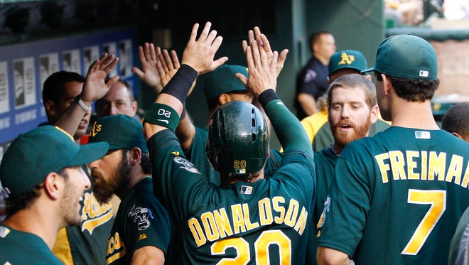 Oakland Athletics third baseman Josh Donaldson (20) is congratulated by teammates in the dugout after scoring a run against the Texas Rangers during the fourth inning  at Rangers Ballpark.